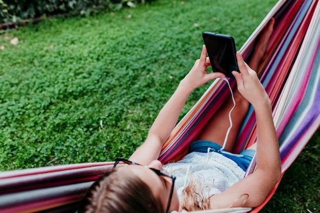 Menina bonita do adolescente que encontra-se na rede colorida no jardim. ouvindo música no celular e fone de ouvido e sorrindo