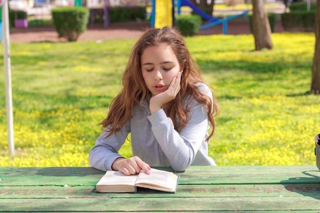 Menina bonita do adolescente que lê um livro e que estuda a lição de casa no parque do verão