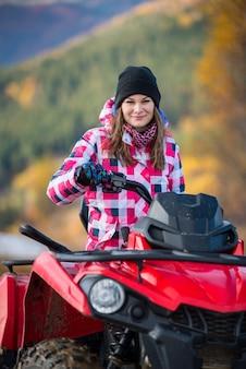 Menina bonita do close-up na roupa do inverno na bicicleta quadriciclo vermelha que olha a câmera na natureza borrada do fundo
