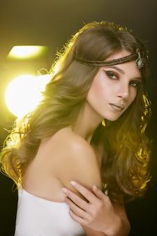 Menina bonita do modelo de forma com composição dourada.