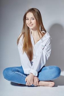 Menina bonita do modelo de moda jovem em jeans azul, sentado no chão