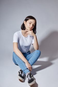Menina bonita do modelo de moda jovem em jeans azul