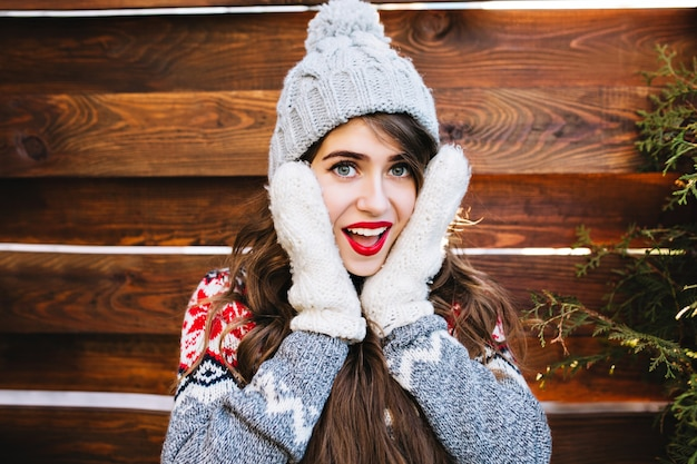 Menina bonita do retrato com cabelo comprido e lábios vermelhos no chapéu de malha na madeira. ela está tocando o rosto com luvas quentes, sorrindo.