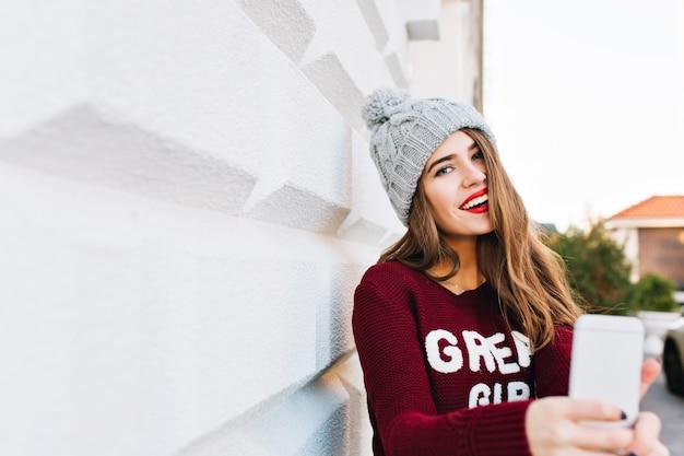Menina bonita do retrato com cabelo comprido na camisola de marsala, fazendo selfie na parede cinza. ela usa chapéu de malha e tem lábios vermelhos.