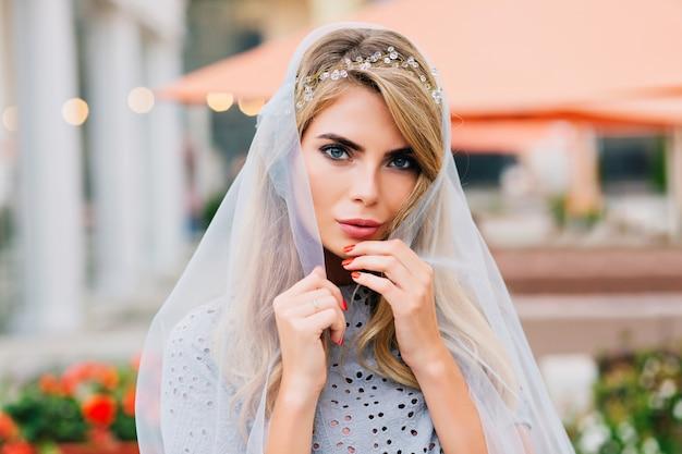 Menina bonita do retrato lá fora no fundo do terraço. ela segura um véu azul cobrindo a cabeça, olhando para a câmera.