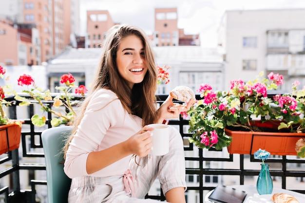 Menina bonita do retrato tomando café da manhã na varanda cercam flores na manhã ensolarada na cidade. ela segura uma xícara, um croissant, sorrindo.