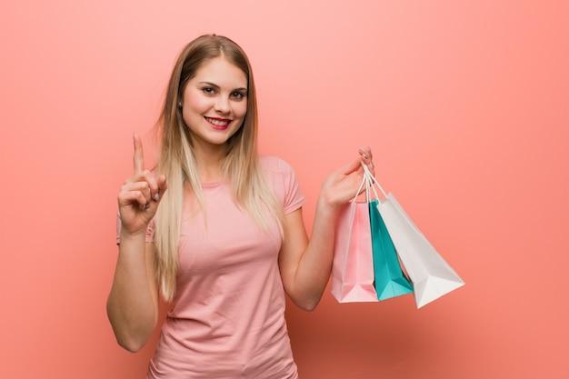 Menina bonita do russo que mostra o número um. ela está segurando uma sacola de compras.