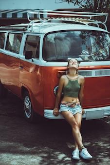 Menina bonita do surfista com van clássico da ressaca do vintage na praia no por do sol