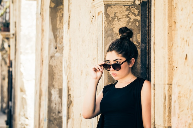 Menina bonita do tennage com óculos de sol