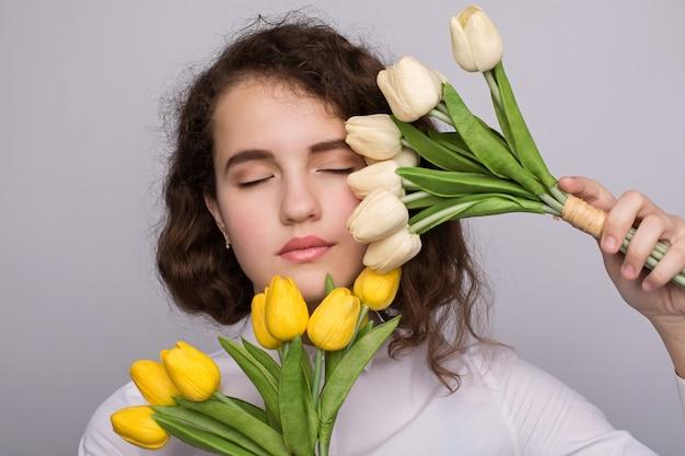 Menina bonita do vestido com tulipas flores nas mãos, sobre um fundo claro