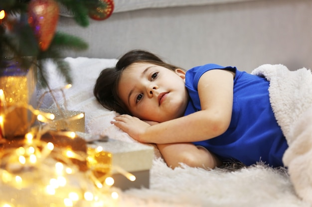 Menina bonita dormindo em um sofá aconchegante em um quarto decorado de natal