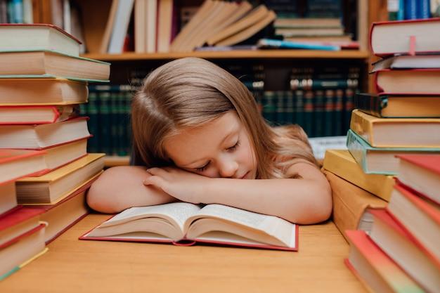 Menina bonita dormindo na biblioteca