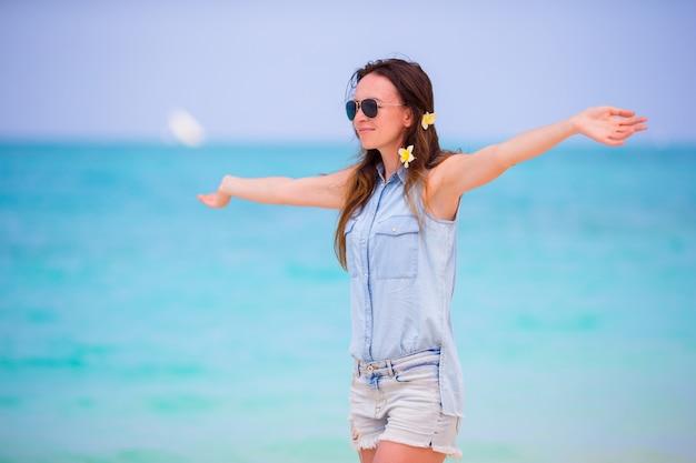 Menina bonita durante férias de praia tropical. desfrute de umas férias sozinhas na praia da áfrica com flores de frangipani no cabelo