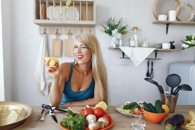 Menina bonita e alegre em uma cozinha com legumes