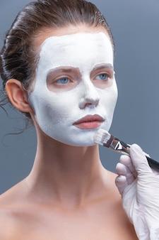 Menina bonita é aplicada uma máscara cosmética branca de pontos pretos isolados
