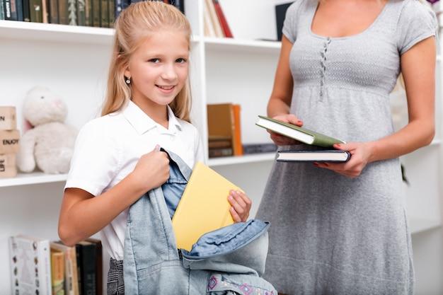 Menina bonita e atraente coloca livros em uma bolsa, a mãe dela a ajuda. preparando para a escola