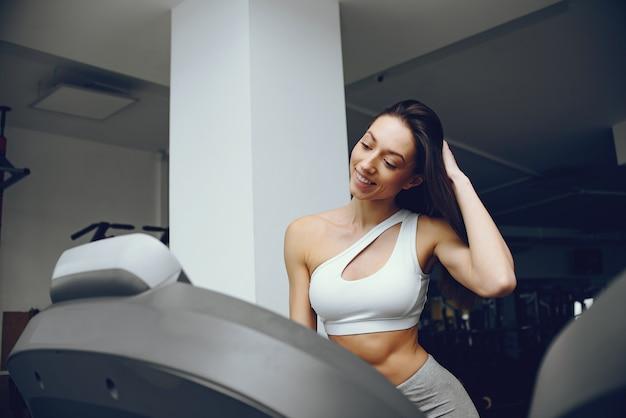 Menina bonita e elegante em pé em um ginásio