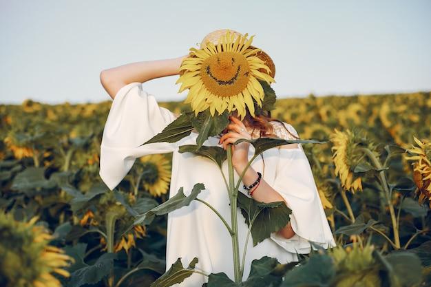 Menina bonita e elegante em um campo com girassóis
