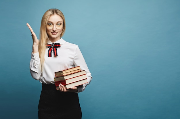 Menina bonita e elegante modelo loiro surpreso em óculos, blusa elegante e saia de renda preta, com pilha de livros posando, isolado