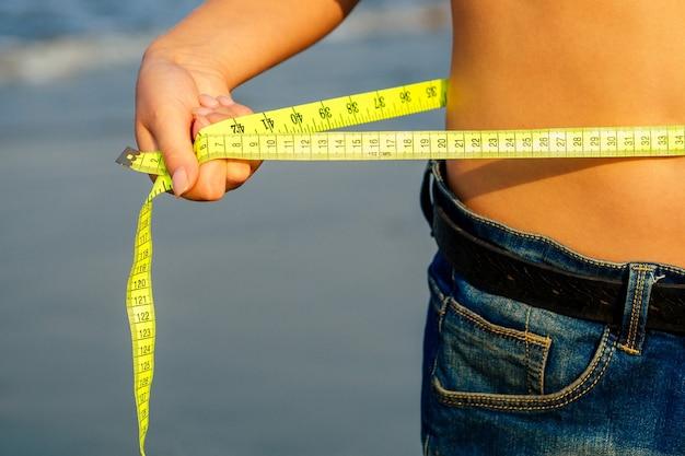 Menina bonita e esbelta em shorts jeans tem na mão uma fita amarela de medição na praia. conceito de desintoxicação e dieta