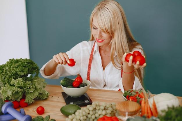 Menina bonita e esportiva em uma cozinha com legumes