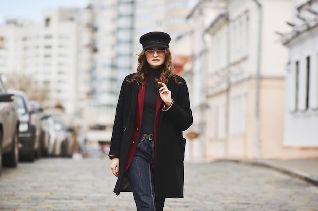 Menina bonita e estilosa, de boné, casaco e óculos escuros, andando pela rua. Foto Premium