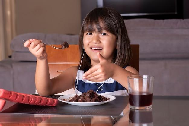 Menina bonita e feliz assistindo tablet e comendo bolo de chocolate