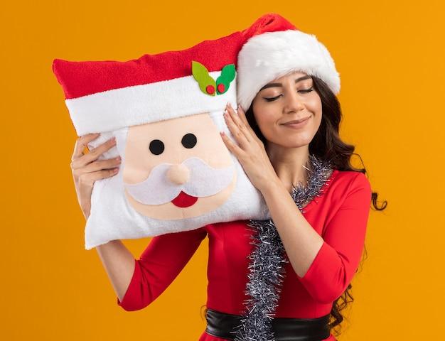 Menina bonita e feliz com chapéu de papai noel e guirlanda de ouropel em volta do pescoço, segurando uma almofada de papai noel, tocando a cabeça com ela com os olhos fechados, isolada na parede laranja