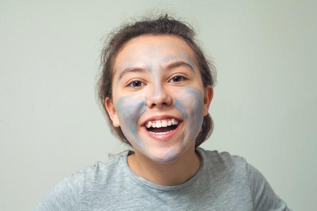 Menina bonita e feliz com uma máscara facial cosmética