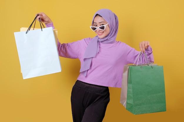 Menina bonita e feliz sorridente usando óculos, segurando sacolas de compras, comprar presentes ou presentes, mimar-se, rir com alegria