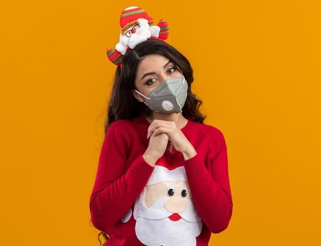 Menina bonita e jovem satisfeita com uma faixa de papai noel e um suéter com máscara protetora, mantendo as mãos juntas isoladas na parede laranja com espaço de cópia