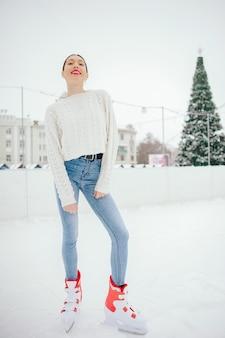 Menina bonita e linda com um suéter branco em uma cidade de inverno