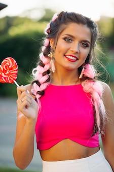 Menina bonita e positiva no topo rosa segurando coração doce na vara.
