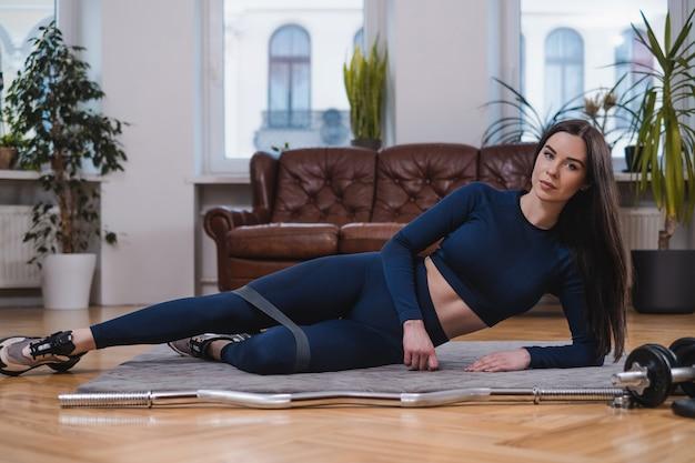 Menina bonita e relaxada em poses de sportswear no tapete com banda de resistência em apartamento com design moderno.