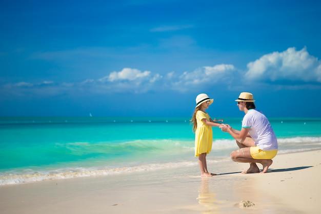 Menina bonita e seu pai na praia exótica tropical