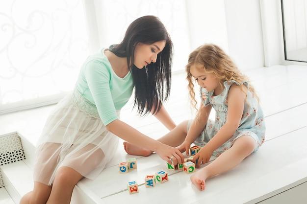Menina bonita e sua mãe jogando e educando com cubos abc dentro de casa. jovem mãe bonita e sua filha jogando blocos.