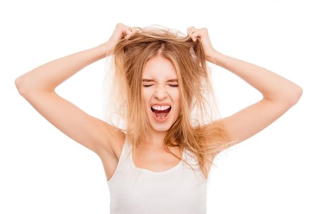 Menina bonita e triste segurando o cabelo danificado e gritando
