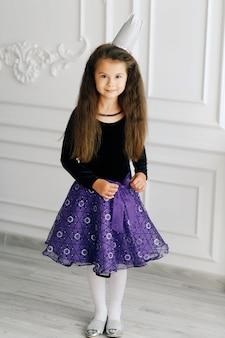 Menina bonita elegante com coroa de brinquedo branco na blusa preta e saia violeta