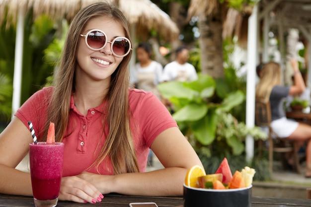 Menina bonita elegante com penteado comprido e sorriso fofo, vestindo uma camisa pólo e óculos de sol redondos, relaxando sozinha em um café na calçada