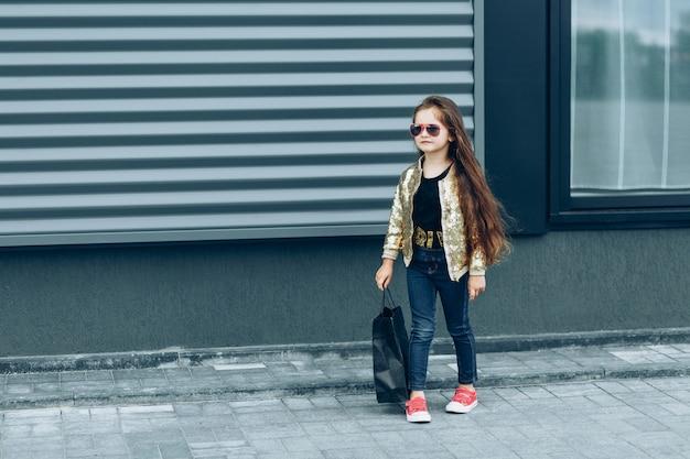 Menina bonita elegante com saco de papel preto, voltando das compras