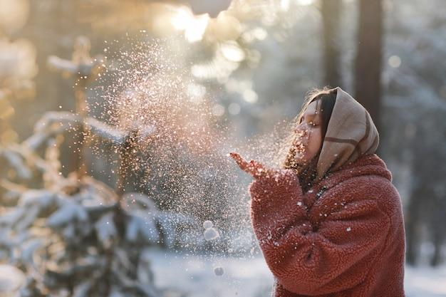 Menina bonita, elegante e jovem, soprando a neve das mãos na floresta de inverno. feriado de natal.