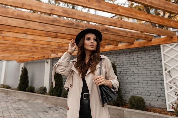 Menina bonita elegante elegante com um chapéu estiloso em um casaco bege da moda com uma bolsa de couro preta anda na rua. estilo feminino e beleza
