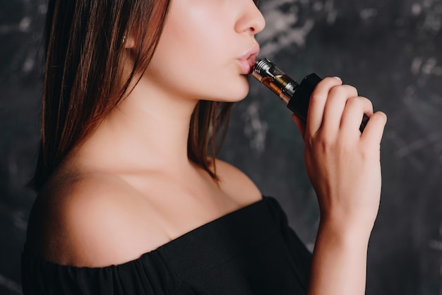 Menina bonita elegante fumar cigarro. metade do rosto, close-up vista. dentro de casa.