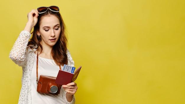 Menina bonita em amarelo olha bilhetes com passaporte