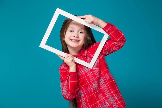 Menina bonita em camisa xadrez com cabelo morena segurar a moldura de imagem