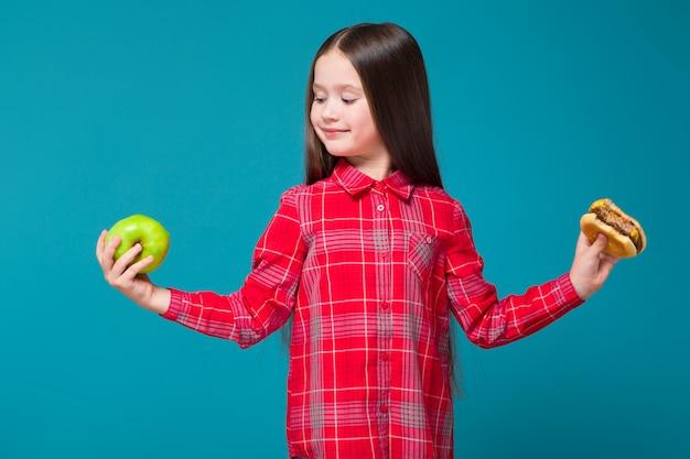 Menina bonita em camisa xadrez com cabelo moreno segurar hambúrguer