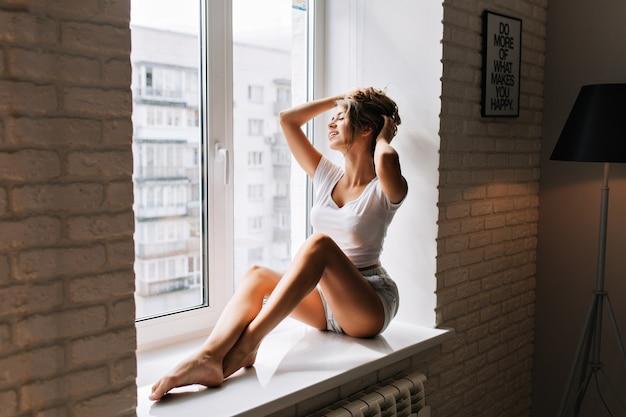 Menina bonita em camisas na janela do apartamento pela manhã. ela tocando o cabelo e sorrindo com os olhos fechados.