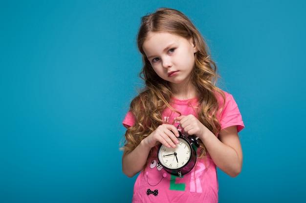 Menina bonita em camiseta com cabelo morena, com relógio nas mãos