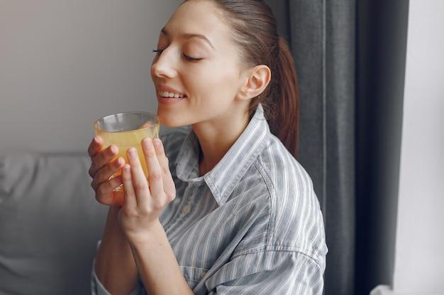 Menina bonita em casa com suco de oranhe
