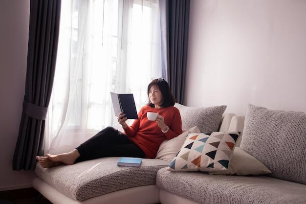 Menina bonita em casa que senta-se no sofá, lendo um compartimento e tendo uma ruptura de café.